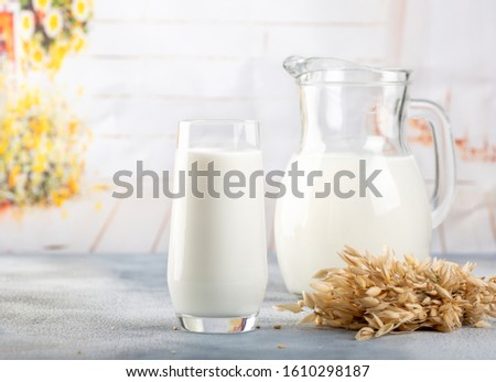 Glass of vegan oat milk and Oat on a table, space for text. Light background #1610298187