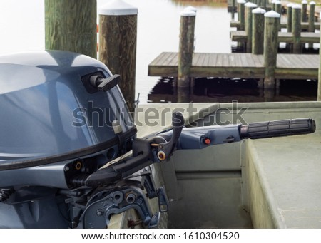 Outboard motor on a boat with boat docks in the background #1610304520