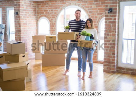 Young beautiful couple moving cardboard boxes at new home #1610324809