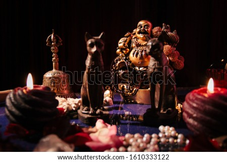 Table with mystical symbols. Buddha figurine, candles, stone rosary, ancient Egypt figurines of cats.  #1610333122