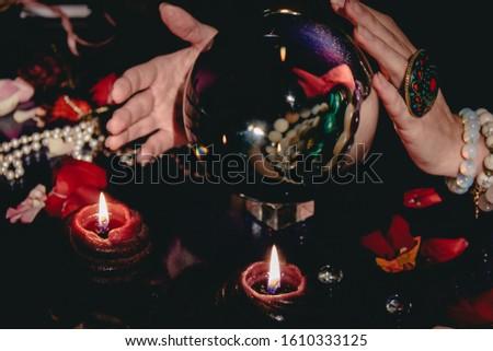 Fortuneteller's hand near a glass orb. Prediction of the future. Mystic interior. Occult symbols #1610333125