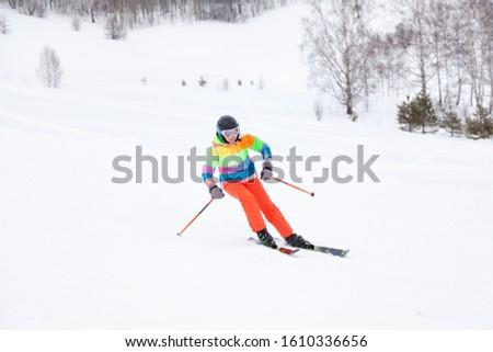 Altai, Russia - 01.01.2020: A woman skier slides down the mountain over white snow in a sports tourist base Turquoise Katun. Seasonal sports. #1610336656