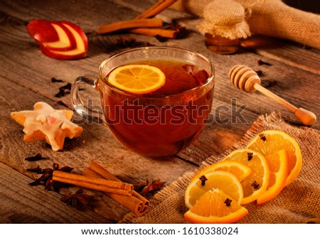 Cup of hot tea on rustic wooden plank with cinnamon stick, orange, lemon, honey, anise, cloves and other warm decoration. Warm colors. #1610338024