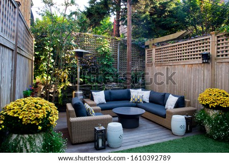 Urban, neutral, outdoor living space exterior photo. Outdoor living room with couch, comfy couch cushions, throw pillows, love seat, chairs and coffee table. Backyard lush with greenery and plants. Royalty-Free Stock Photo #1610392789