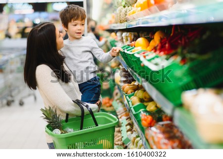woman and child boy during family shopping with trolley at supermarket #1610400322