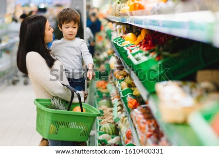 Mother with son at a grocery store #1610400331