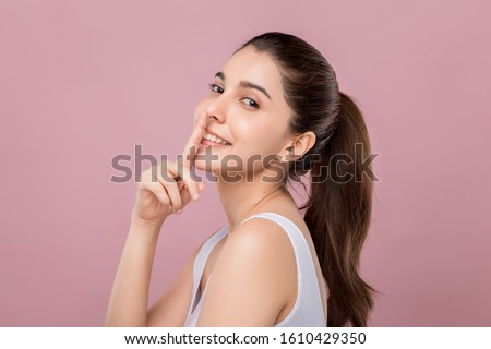 Young beautiful Caucasian woman with smiley face touching her nose, surgery nose job concept, isolated on pink background. #1610429350