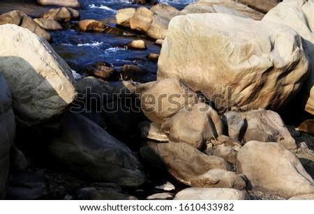 Beautiful scenic view of flowing water between stones in Uttarakhand, India.   #1610433982
