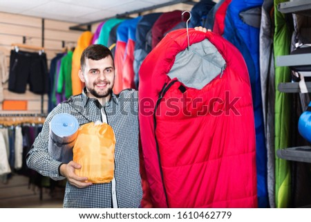 Young smiling cheerful positive man choosing touristic equipment in sports equipment store  #1610462779