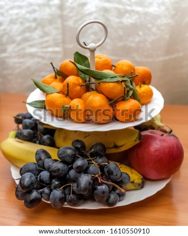 Tangerines with leaves, bananas, Apple and dark grapes close-up on a white two-tiered plate on a table background curtain #1610550910
