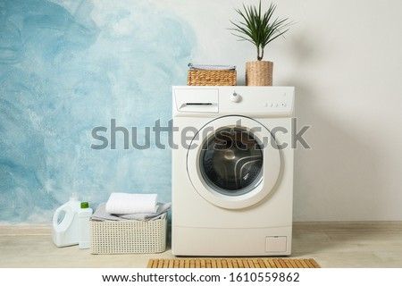 Laundry room with washing machine against light blue wall, space for text #1610559862