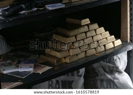 Money bags, currency and the stack of gold blocks on the strongbox shelves. #1610578819