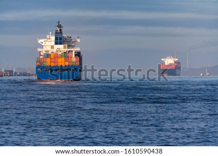 Two Vessels with Containers leaving and arriving at Hamburg Harbour meeting each other on the River Elbe as symbol of global Trade and international water traffic #1610590438