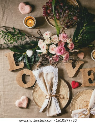 st. Valentines day or wedding romantic table setting with wooden letters love, needle felted hearts, bouquet of pink roses and red grapes on natural linen tablecloth. Flat lay #1610599783