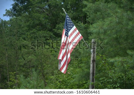 American flag flying on a flagpole next to an outhouse #1610606461