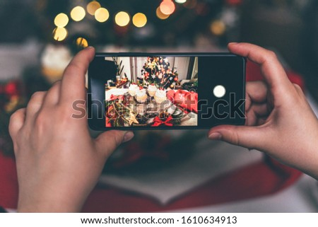 Female hands take a picture on the phone of cupcakes on the table with fir tree branches decoration and bokeh lights. Close up.
