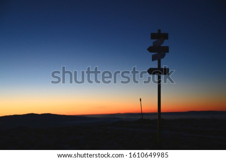 Silhouette of arrows in mountains, sunrise light in background. Arrows showing right direction #1610649985
