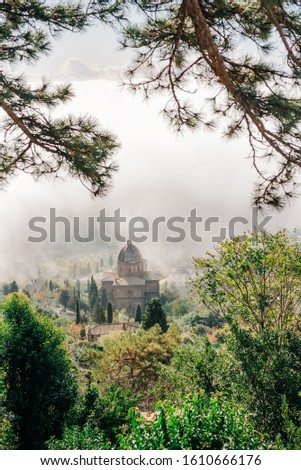 The ancient city of Cortona in Italy, in Tuscany. Tuscany medieval churches on green background of italian nature #1610666176