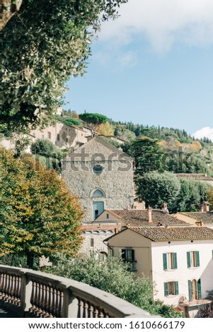 The ancient city of Cortona in Italy, in Tuscany. Tuscany medieval churches on green background of italian nature #1610666179