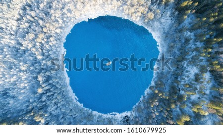 Aerial view of the winter lake with clear blue sea water and boat. Abstract picture. Above captured with a drone. Beautiful snowy forest.