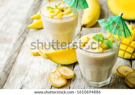 banana mango smoothie on a wood background. toning. selective Focus #1610694886
