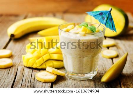 banana mango smoothie on a wood background. toning. selective Focus #1610694904