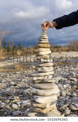 Hand putting the last stone on a pebble (stone tower). Hapiness and tranquility. Meditation and zen #1610696365