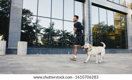 Young black man running with his white labrador dog in buseness city center during beautiful fall morning #1610706283