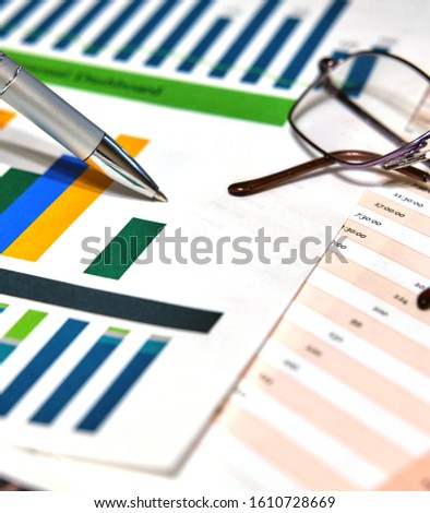 Calculation charts, business charts. Pen and glasses. #1610728669