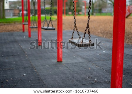 a set of swings in a child's playground or park with the focus on the first swing  #1610737468