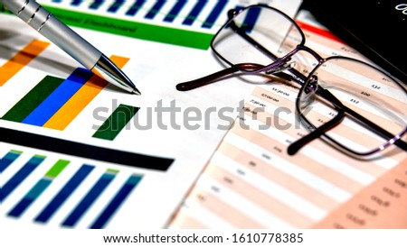 Calculation charts, business charts. Pen and glasses. #1610778385