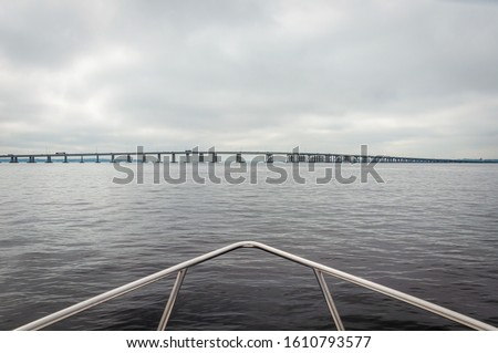 View of the bow of a fishing boat heading towards a Jacksonville bridge, on a rainy and overcast morning, Florida, USA. #1610793577