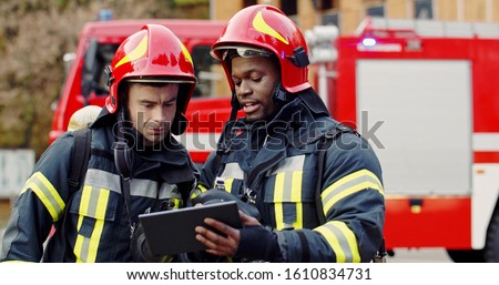 Portrait of two firefighters in fire fighting operation, fireman in protective clothing and helmet using tablet computer in action fighting.  #1610834731