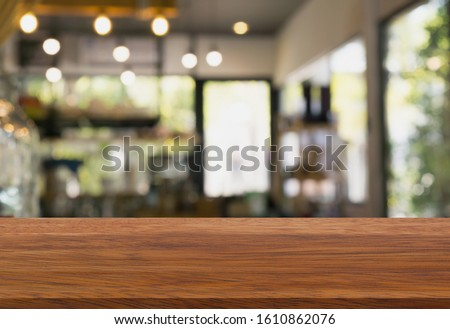 Wood table top on blur cafe interior background. #1610862076