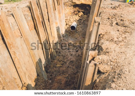 Construction site of an underground oil and gas pipeline.Work of burying oil and gas supply pipeline.work on the pipe laying of the pipelines in a special corrosion-resistant insulation in the trench #1610863897