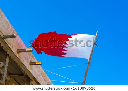 National flag of Qatar on a flagpole in front of blue sky. #1610898526