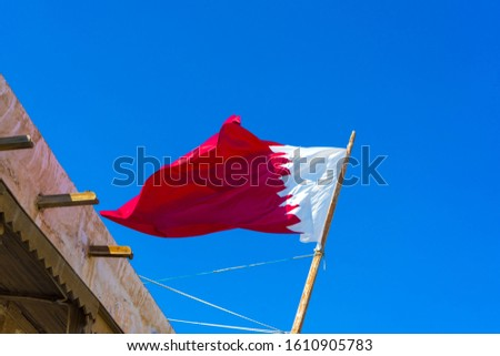 National flag of Qatar on a flagpole in front of blue sky. #1610905783