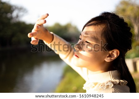Asian child girl covering face by hand to protect,prevent face skin from bright sun in outdoor summer,female people hand covered the strong sun light feeling hot uncomfortable,risk of eyes damage  #1610948245