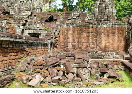 Ta Prohm in summer sunny day, pile of bricks and stones against the background of an ancient building horizontal photo, brown volcanic porous rock #1610951203