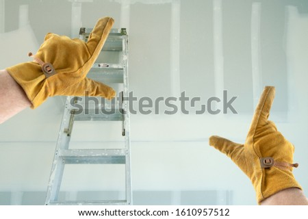 Contractor Hands In Leather Gloves Framing New Blank Drywall. #1610957512