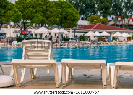 Plastic white plank beds for suntan at hotel standing with umbrellas chaise lounges near the pool. #1611009967