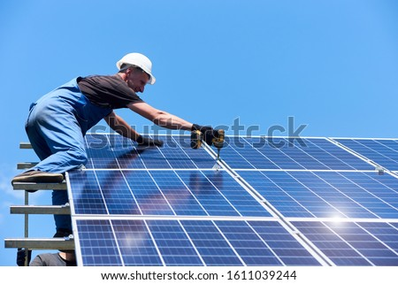 Man mounting modern solar batteries on house's roof. Using high ladder and professional drill. Environment friendly, green energy. Ecological. Using natural renewable energy. Wearing work uniform. #1611039244