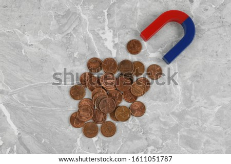 Magnet attracting coins on grey marble table, flat lay #1611051787