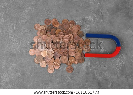 Magnet attracting coins on grey stone table, flat lay #1611051793