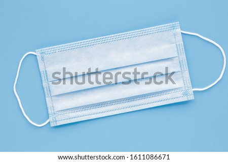 Surgical mask with rubber ear straps. Typical 3-ply surgical mask to cover the mouth and nose. Procedure mask from bacteria. Protection concept. #1611086671