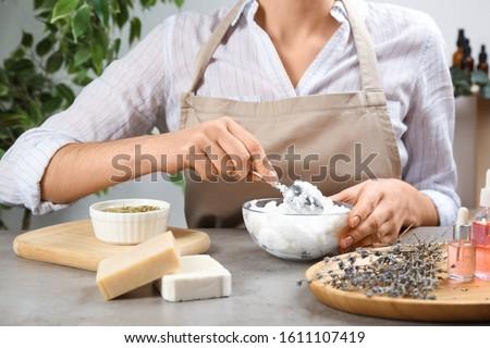 Woman making natural handmade soap at grey stone table, closeup Royalty-Free Stock Photo #1611107419