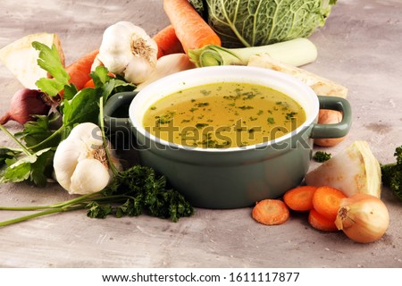 Broth with carrots, onions various fresh vegetables in a pot - colorful fresh clear spring soup. Rural kitchen scenery vegetarian bouillon