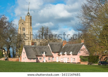 Thatched cottage painted inpink with St. Mary the Virgin's Church on the village green.  #1611169681