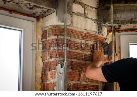 The use of aluminum rails for preparing walls for applying plaster. Installation of guides for plaster. Installation of metal lighthouses on a brick wall. #1611197617