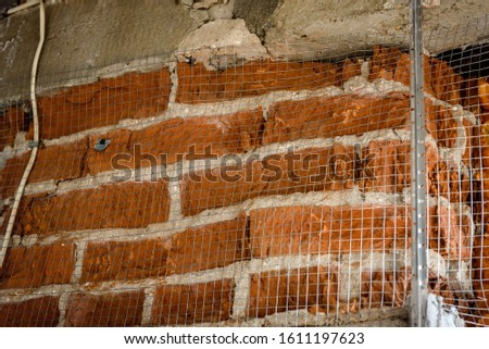 The use of aluminum rails for preparing walls for applying plaster. Installation of guides for plaster. Installation of metal lighthouses on a brick wall. #1611197623